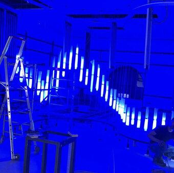 Blau beleuchteter Raum mit weißen Lampen, die das DBG Logo bilden